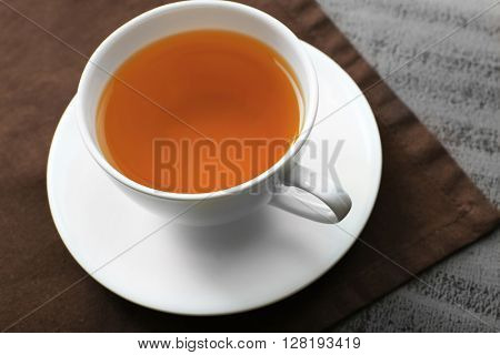 Cup of tea on brown napkin