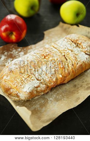 Strudel with apples, walnut and raisins on parchment