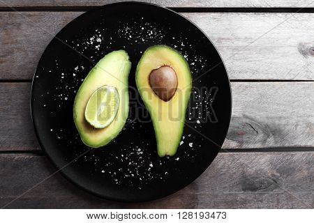 Sliced avocado with lime and salt on black plate