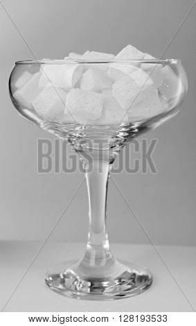 Margarita glass filled with lump sugar on grey background