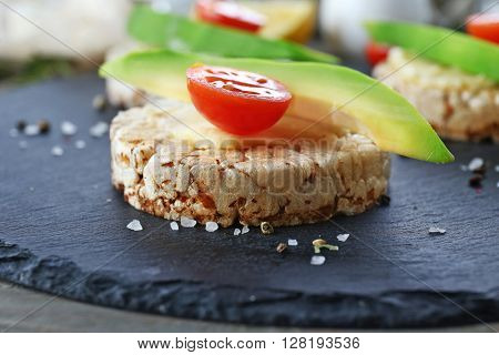 Avocado sandwiches with tomatoes on a mat