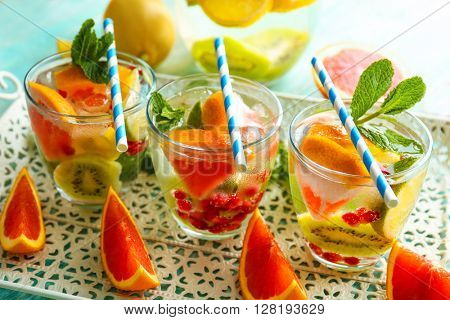 Refreshing cocktails with ice, mint, pomegranate seeds and slices of fruits on a tray