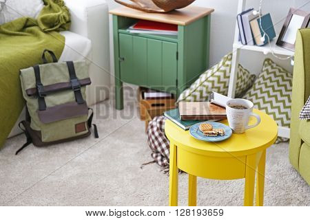 Cup of coffee with biscuits on table in interior of living room