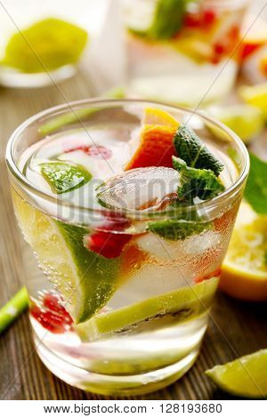 Refreshing cocktail with ice, mint, pomegranate seeds and slices of fruits on wooden background