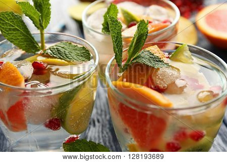 Refreshing cocktails with ice, mint, pomegranate seeds and slices of fruits