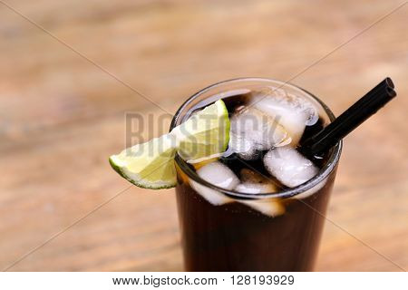 Cocktail with lime slices and ice blocks on wooden table, close up