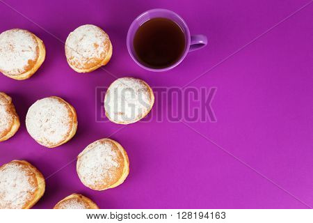 Delicious donuts with powdered sugar and cup of tea on purple surface, top view