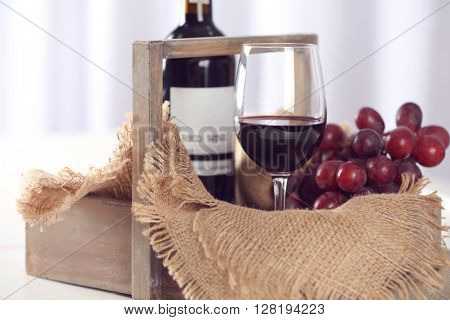 Glass and bottle of red wine with grape on table closeup