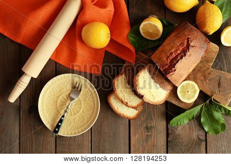 Delicious sweet cake bread with lemons on wooden table, top view