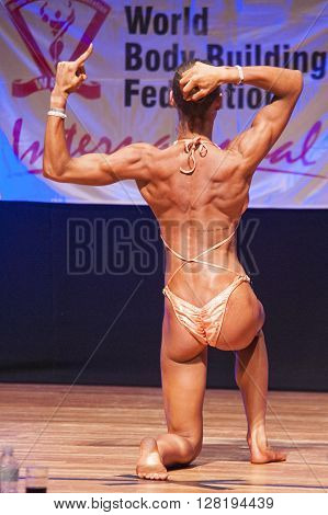 MAASTRICHT THE NETHERLANDS - OCTOBER 25 2015: Female fitness model flexes her muscles and shows her best physique in a back pose on stage at the World Grandprix Bodybuilding and Fitness of the WBBF-WFF on October 25 2015 at the MECC Theatre in Maastricht