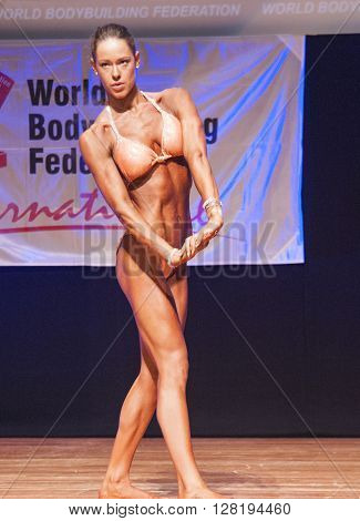 MAASTRICHT THE NETHERLANDS - OCTOBER 25 2015: Female fitness model flexes her muscles and shows her best physique in a chest pose on stage at the World Grandprix Bodybuilding and Fitness of the WBBF-WFF