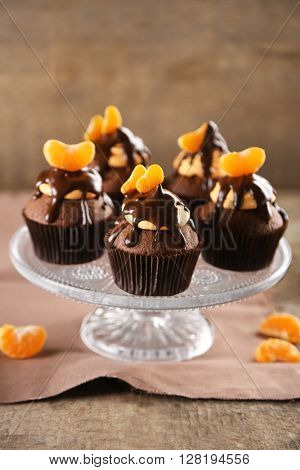 Tasty cupcakes with slice of mandarin and chocolate on wooden background