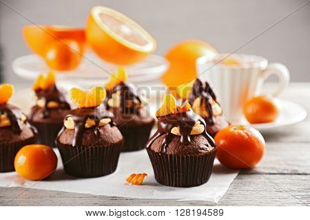 Tasty cupcakes with slice of mandarin and chocolate on a paper over light wooden background
