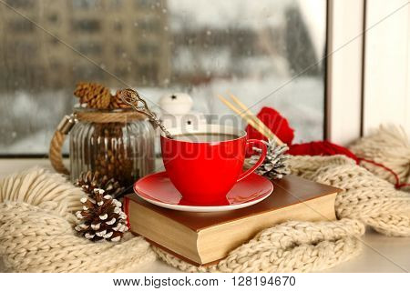 Cup of hot drink in on the windowsill in living room. Comfortable winter weekend or holidays at home