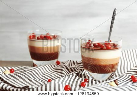 Delicious dessert with rowan in glass on table