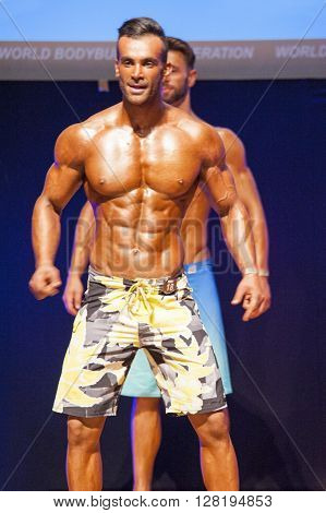 MAASTRICHT THE NETHERLANDS - OCTOBER 25 2015: Male physique model shows his best front pose at championship on stage at the World Grandprix Bodybuilding and Fitness of the WBBF-WFF on October 25 2015 at the MECC Theatre in Maastricht the Netherlands