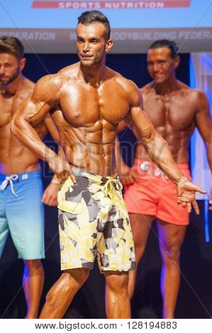 MAASTRICHT THE NETHERLANDS - OCTOBER 25 2015: Male physique model shows his best side pose at championship on stage at the World Grandprix Bodybuilding and Fitness of the WBBF-WFF on October 25 2015 at the MECC Theatre in Maastricht the Netherlands