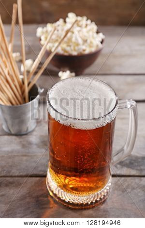 Glass mug of light beer with snacks on wooden table, close up