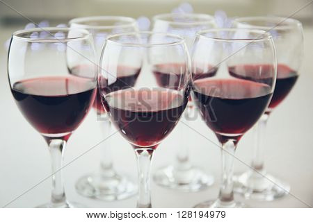 Glasses of red wine on white table closeup