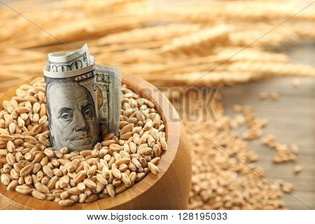 Dollar banknotes and wheat grains in bowl on wooden background. Agricultural income concept