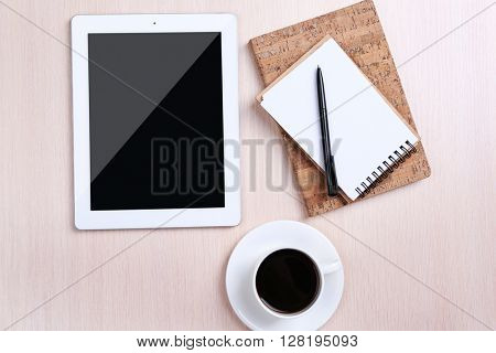 Tablet with cup of coffee and notepad on wooden table