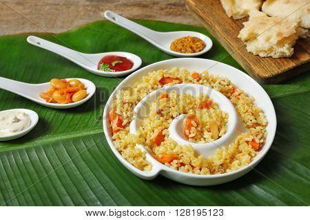 Fried rice with flat bread and spices on banana leaf background
