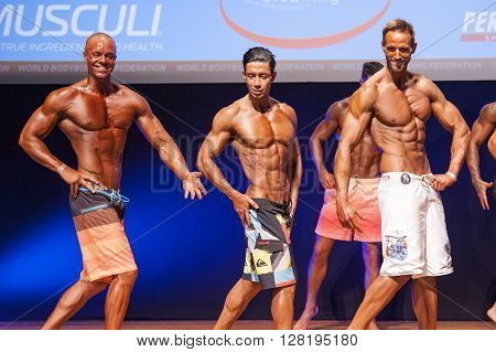 MAASTRICHT THE NETHERLANDS - OCTOBER 25 2015: Male physique models Ali Dalili from Iran and others show their best front pose at championship on stage at the World Grandprix Bodybuilding and Fitness of the WBBF-WFF on October 25 2015 at the MECC Theatre