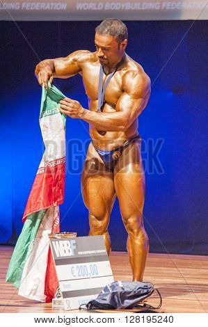 MAASTRICHT THE NETHERLANDS - OCTOBER 25 2015: Male bodybuilder celebrates his victory on stage with his national flag of Iran at the World Grandprix Bodybuilding and Fitness of the WBBF-WFF on October 25 2015 at the MECC Theatre in Maastricht