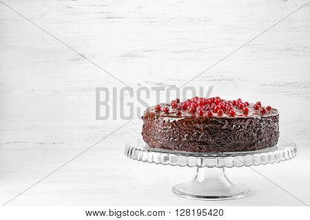 Chocolate cake with cranberries on wooden background
