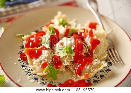 Cooked ravioli with tomato sauce on plate