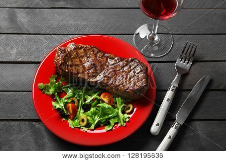 Grilled steak with vegetable salad and glass of wine, closeup