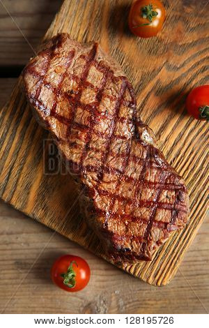 Grilled steak on cutting board with cherry tomatoes, closeup