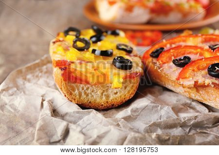 Hot pizza baguettes with olives, paprika, ham and salami on wooden table