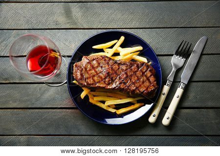 Grilled steak with french fries and glass of wine, closeup
