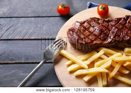 Grilled steak with french fries and cherry tomatoes, closeup