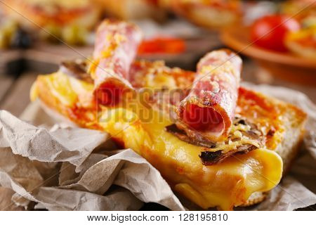 Hot pizza baguette with bacon, mushrooms and cheese on wooden table