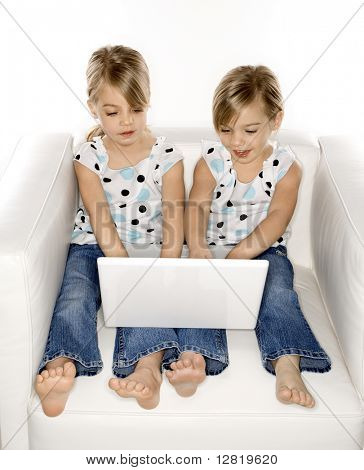 Female children Caucasian twins playing with laptop computer.