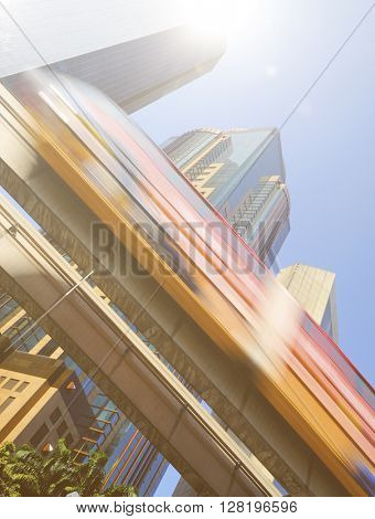 Motion blur of a skytrain speeding through a modern business district.