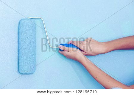 Female hand painting wall with paint roller