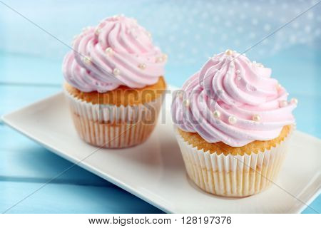 Pink cupcakes on wooden background