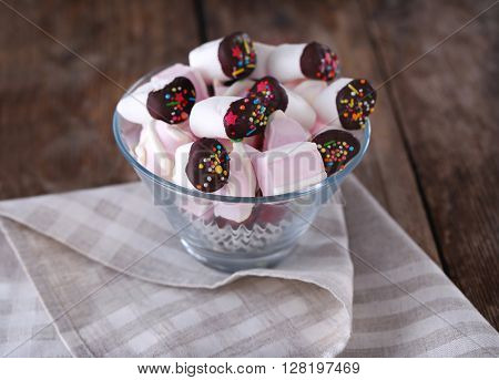 Tasty marshmallows with chocolate on old wooden table, close up