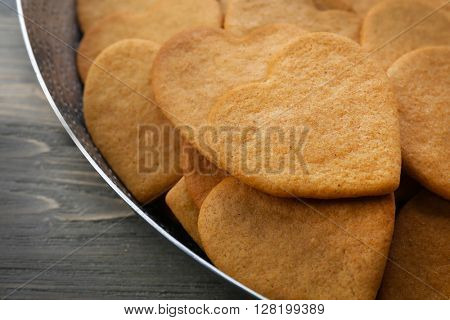 Heart shaped biscuits in baking tray, closeup