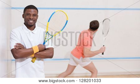 Two men playing match of squash. Back and front views of squash players in action reaching on squash court.