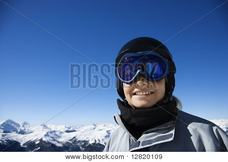 Caucasian teenage boy snowboarder wearing helmet and goggles on mountain looking at viewer Whistler, British Columbia, Canada.