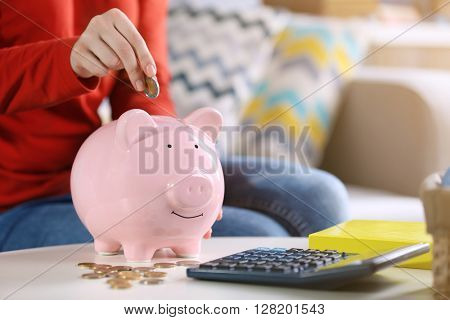 Female hand putting coins into piggy bank closeup
