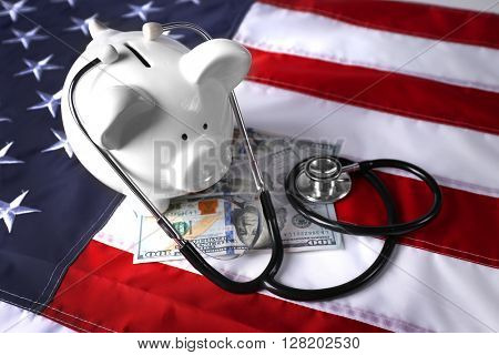 Stethoscope with dollar banknotes and piggy bank on background of USA flag