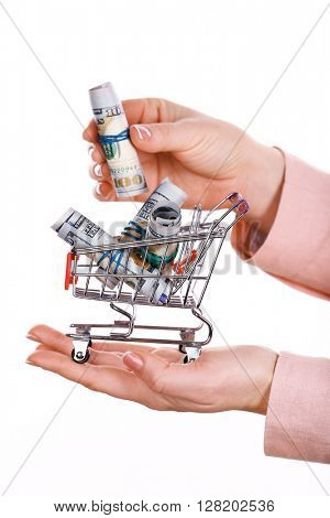 Woman holding supermarket trolley full of money, isolated on white