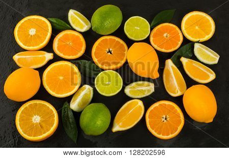Lime lemon orange and tangerine on black background. Fresh food. Ripe fruit. Citrus fruit. Vegetarian food. Mixed fruit. Fresh fruit.