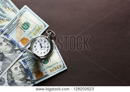 Time is money concept with pocket watch and dollars bills on brown background