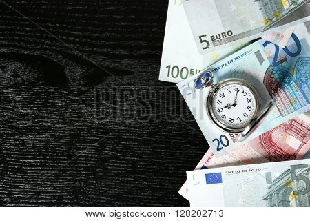 Time is money concept with pocket watch and euros bills on wooden table, top view
